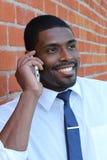 Etniczny Młody biznesmen Na zewnątrz biura Na telefonie komórkowym Fotografia Royalty Free