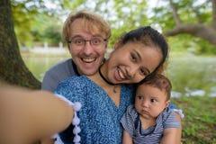 Etniczny młody rodzinny spajać wpólnie przy parkiem zdjęcia stock