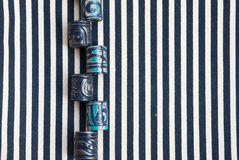 Etnika. Abstract background with marine jewellery beads on striped fabric. Handmade blue jewellery beads from polymer clay royalty free stock photo