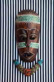 Etnika. African jewelry necklace with african, asian, thai mask on striped fabric. Handmade tribal jewelery from polymer clay royalty free stock photo