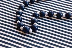 Etnika. Aquamarine background, sea, blue and white beads and striped fabric stock image