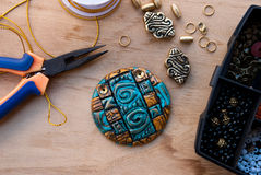 Etnika. Assembly of jewelry of polymer clay in egypt style with gold elements and box with small beads. Hobby, handicraft. Pilers with unfinished necklace royalty free stock images