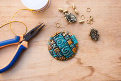 Etnika. Assembly of jewelryof polymer clay in egypt style with gold elements. Hobby, handicraft. Pilers with unfinished necklace royalty free stock photo