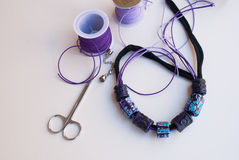 Etnika. Assembly of polymer clay jewelry.Unfinished necklace in ethnic style with scissors and decorative cords stock image