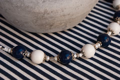 Etnika. Background with elegant beads blue and white, ceramic bowl and stripped fabric. Polymer clay jewelry royalty free stock photography