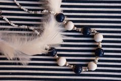 Etnika. Background with elegant beads blue and white, Feathers and stripped fabric. Polymer clay jewelry royalty free stock images