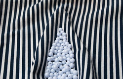 Etnika. Background with objects. Striped fabric with pile of white beads. Sea wallpaper.Unique backdrop royalty free stock photography