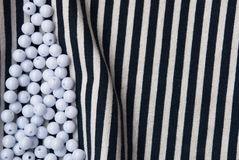 Etnika. Background with objects. Striped fabric with pile of white beads. Sea wallpaper.Unique backdrop stock image