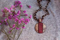Etnika. Background with pink flowers and african pendant. Handmade jewelry of polymer clay royalty free stock image
