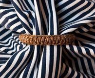 Etnika. Background with striped fabric and handmade born bracelet. Background with jewelry. Marine, sea. Polymer clay royalty free stock image