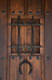Etnika. Background wooden door with grille and horseshoe.Brown old door royalty free stock images