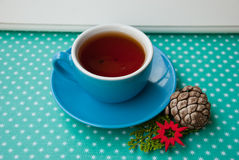 Etnika. Blue cup with british tea with new year decor on green background with snowflakes Stock Images