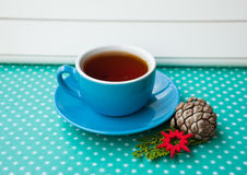 Etnika. Blue cup with british tea with new year decor on green background with snowflakes Stock Photos