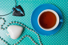 Etnika. Blue Cup of tea on green background with white points, jewelry pendant, heart .Beautiful color. New Year still life top view objects Royalty Free Stock Photography