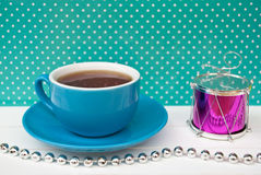 Etnika. Blue Cup of tea on green background with white points and small decor drum. Beautiful color. New Year still life Royalty Free Stock Images