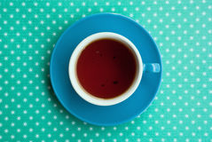 Etnika. Blue Cup of tea on green background with white snowflakes. Beautiful color Royalty Free Stock Photo