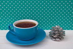 Etnika. Blue Cup of tea on green background with white snowflakes and small decor silver pine. Beautiful color. New Year still life Stock Photo