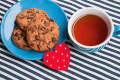 Etnika. Blue cup of tea and plate with cookies with chocolate on striped fabric and small heart. Classical breakfast still life in marine style.Valentines day Royalty Free Stock Images