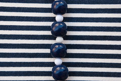 Etnika. Blue and white Beads on striped fabric. Background with jewellery. New backdrop.Marine wallpaper royalty free stock images