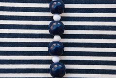 Etnika. Blue and white Beads on striped fabric. Background with jewellery. New backdrop.Marine wallpaper stock images