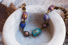 Etnika. Bohemian jewelry beads in grey ceramic pot. Handmade jewelry from polymer clay. Colorful necklace in indian style stock photography