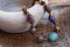 Etnika. Bohemian jewelry beads with grey ceramic pot. Handmade jewelry from polymer clay. Colorful necklace in indian style stock photos