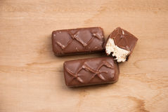 Etnika. Chocolate covered bars with milk mouse on wooden desk stock photos