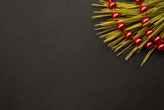 Etnika. Christmas or New Year photo background. Black paper board closeup with pine brunch and red garland.  Frame image for seasonal greeting card, discount or Stock Photos