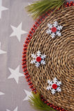 Etnika. Christmas and New Years handmade background with straw support, garland, snowflakes, brunch of new year tree  on fabric with stars.Copy space. Place for Stock Image