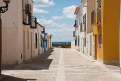 Etnika. Desert street on Tabarca Island Spain with blue sky and beautiful clouds and many colorful houses royalty free stock image