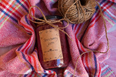 Etnika. Ecological homemade strawberry jam in glass jar with rope on colorful kitchen towel. Food still life top view royalty free stock image