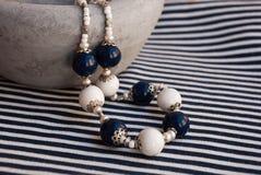 Etnika. Elegant beads white blue with pearls scandinavian style on big ceramic bowl on stripped fabric. Marine jewelry. Handmade jewelry of polymer clay royalty free stock photos