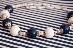 Etnika. Elegant beads white blue with pearls scandinavian style. Marine jewelry. Handmade jewelry of polymer clay stock image