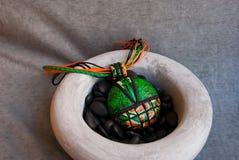 Etnika. Green orange jewelry pendant in ceramic bowl with small black stones. Still life. Handmade jewelry of polymer clay royalty free stock photos