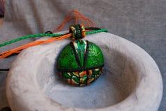 Etnika. Green orange jewelry pendant in ceramic bowl. Still life. Handmade jewelry of polymer clay royalty free stock photography