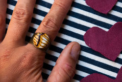 Etnika. Hand with handmade ring of polymer clay on striped fabric and hearts.Background with jewelry stock photo