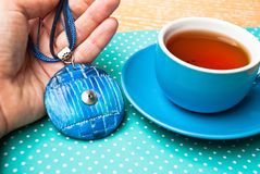 Etnika. Hand with unexpected morning gift necklace from polymer clay and cup of tea. Handmade jewelry. Top view Stock Photography