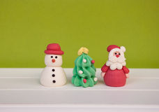 Etnika. Handmade figures santa claus, new year tree and snowman on white wooden shelf and green background. New year and christmas card Royalty Free Stock Photo