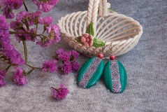 Etnika. Handmade jewelry, green earrings, interesting, made of polymer clay, african style. Still life with earrings, pink flowers and ceramic vase stock photography