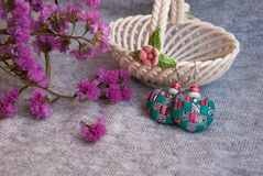 Etnika. Handmade jewelry, green earrings, interesting, made of polymer clay, african style. Still life with earrings, pink flowers and ceramic vase royalty free stock photo