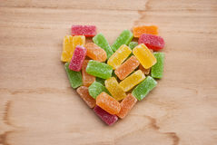Etnika. Heart of jelly colorful sweets on wooden background stock images