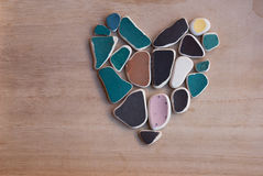 Etnika. Heart from sea pebbles on wooden background royalty free stock image