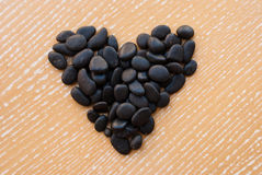 Etnika. Heart from small sea stones on wooden table. Top view. Love concept royalty free stock photo