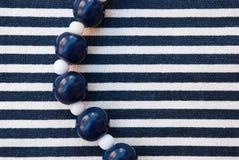 Etnika. Jewellery Beads Aquamarine and white on striped fabric. Blue Line. Denim, sea.Handmade jewellery of polymer clay stock photo