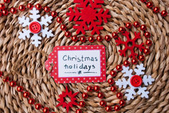 Etnika. Label  handmade on wattled straw support with red snowflakes and garland, Text Christmas holidays, New year event Stock Image