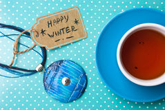 Etnika. Label with text happy winter, jewelry pendant gift and blue cup of tea on green background. Banner, sale, card Royalty Free Stock Photography