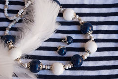 Etnika. Luxury elegant jewelry silver blue white beads and earrings on striped fabric with feathers. Handmade jewelry of polymer clay royalty free stock photography