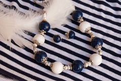 Etnika. Luxury elegant jewelry silver blue white beads and earrings on striped fabric with feathers. Handmade jewelry of polymer clay stock photo