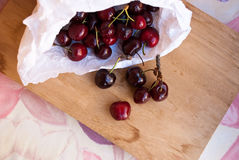 Etnika. Many cherries in white paper bag on wooden desk. Red ripe cherries. Top view stock photos