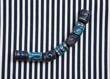 Etnika. Marine jewellery beads on striped fabric. Handmade blue beads from polymer clay royalty free stock photography